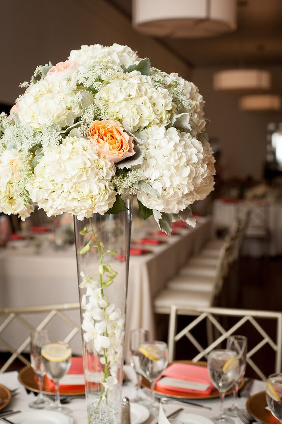 White Hydrangea, Peach Garden Rose, Queen Annes Lace and Dusty Miller sat on top of a tall Trumpet Vase with White submersed Dendrobium Orchids.