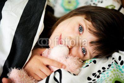 Portrait of awaken little girl in bed