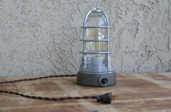 This industrial table lamp is made of aluminum alloy, with a glass shade and cage cover.  This is a rotary switch installed on the side wall of the base. Overall size:  Height: around 9  Diameter: 4-3/4  E26 Porcelain socket, accepts standard bulbs up to 150W, but I suggest 60W max, to protect overheat, although I drill two holes on the bottom to release heat  6 feet brown rayon covered cord with end plug.  Bulb is not included.  Items are handmade, so the piece you purchase may have slight…