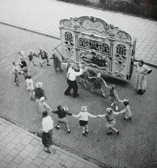 Children dancing next to a barrel organ in Amsterdam, Netherlands, c. 1950