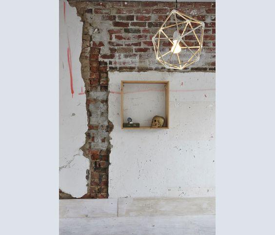 La parete scrostata e segnata della cucina ben descrive il tipo di intervento degli architetti australiani
