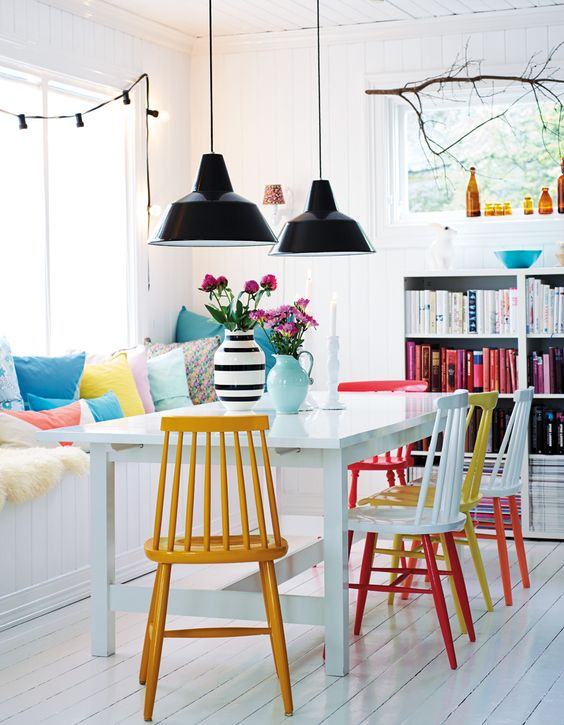"""""""A series of painted dining chairs, colour-coordinated books and paste-coloured cushions bright a bright and friendly atmosphere to this Norwegian dining room."""" @Bright.Bazaar /"""