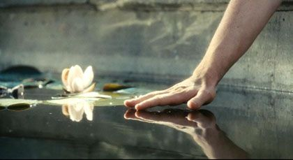 Robbie's hand touching the surface of the water of the fountain in Atonement: