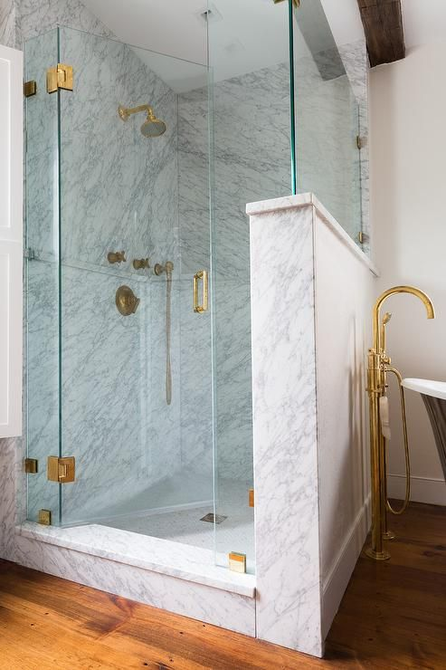A Seamless Glass Door Accented With Antique Brass Hinges Opens To A Walk In Shower B Bathroom Shower Design Frameless Shower Doors Glass Shower Doors Frameless