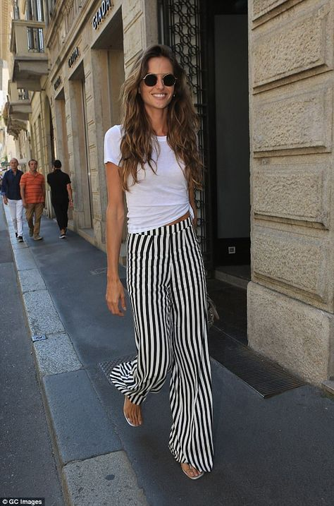 Off-duty model chic: The Brazilian supermodel flashed a peek of her toned stomach in a knotted white T-shirt and striped palazzo pants