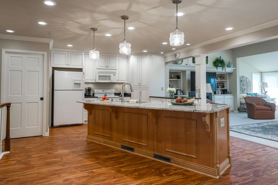 Open concept kitchen with large island, granite top, pendant lights.