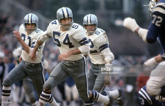 All- Pro linebacker Chuck Howley (54) and safety Mike Gaechter (27) block for linebacker Dave Edwards (52), after Edwards' interception against the Baltimore Colts in 1967.