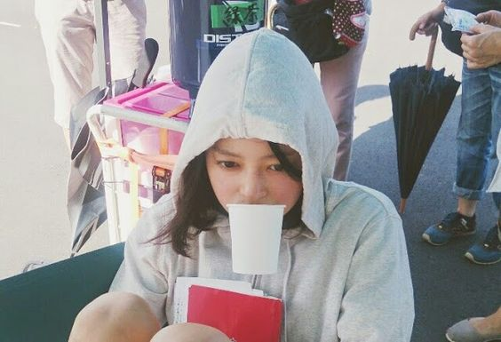 白いパーカーの帽子をかぶってカップを咥えている小林涼子の画像