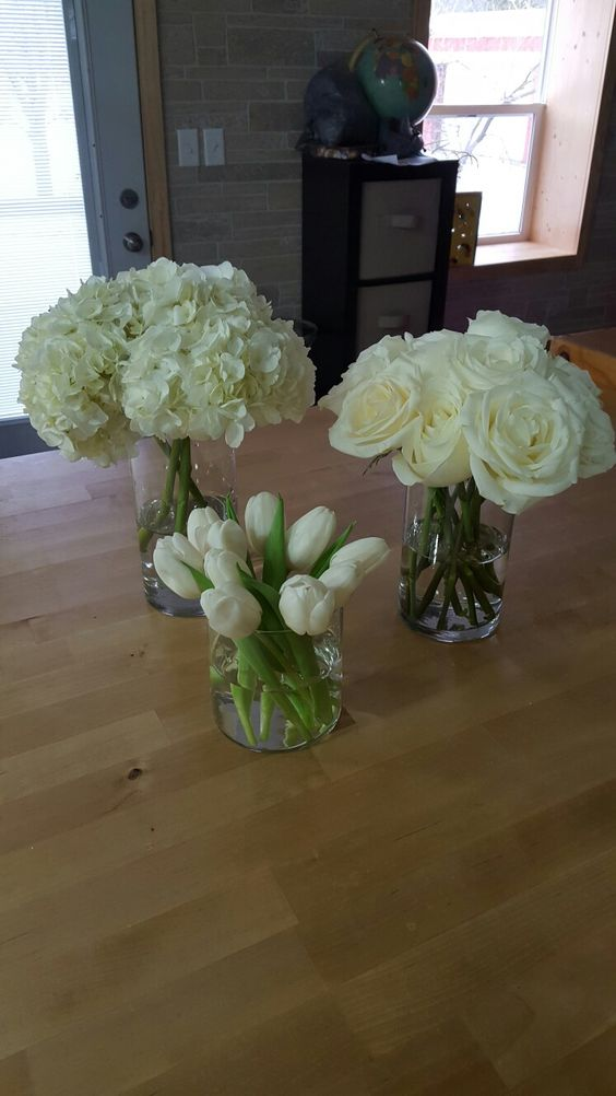 group centerpiece using white roses, tulips, hydrangeas.