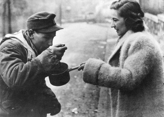 Ungarin gibt einem deutschen Soldaten in Budapest zu essen, 1945.