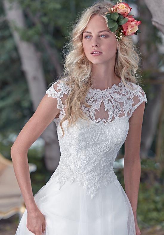 A stunning illusion lace neckline takes center stage in this ball gown wedding dress, with enchanting lace bodice and flowing tulle skirt. A breathtaking illusion lace keyhole back adds a dose of drama. Finished with dainty cap-sleeves and zipper closure.