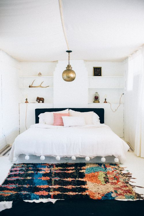 Super boho style bedroom interior. Love the Moroccan rug and the pom pom duvet!