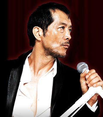 白いシャツにジャケットを着た無精ひげの生えている矢沢永吉の画像