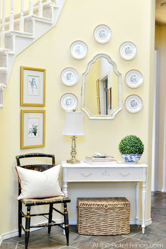 Entry table and chairs. Love the plates on the wall. atthepicketfence.com