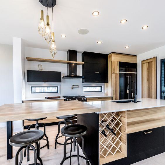 Une cuisine noire, bois et blanc chaleureuse avec rangements pour les bouteilles de vin