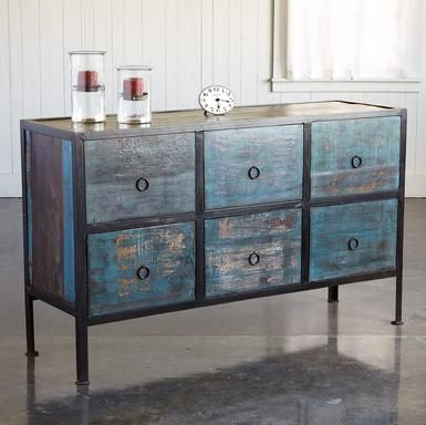 """Reclaimed wood with decades of character begins a modern life in distressed black and turquoise as refreshing as a Bahamian beach. Six deep drawers stash all those hard to store items, even scads of files. Wrought iron ring pulls. Imported. Exclusive. Ships from our supplier in 2 to 4 weeks. Additional shipping, $400. 60""""W x 18""""D x 36""""H."""