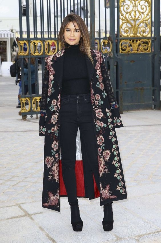 Miroslava Duma in a black embroidered Valentino coat worn with a black turtleneck and skinny jeans: