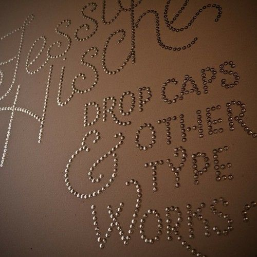 Easy!  Print out the saying you love, go to a copy shop and use a copier to make it as large as you want, tape to wall, then use that as your stencil for thumb-tack art.  Rip the paper away, and you're done!   You could also use nail head trim that is used for furniture!