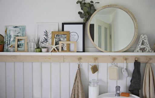 A Mirror Plants Pictures And Shells On A Bathroom Shelf With Hooks Underneath Bathroom Themes Bathroom Wall Decor Simple Bathroom