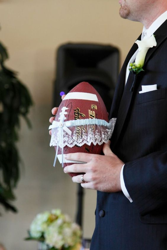 """Put A New Twist On Old Traditions Taking old traditions and changing them up is always a fun way to make your party stand out. In this case the groom took the garter and put it around a football for the garter toss. Go long, groomsmen! Photo via <a href= """"http://www.adaytorememberca.com/blog/football-garter-toss/""""target=_blank"""">A Day To Remember ."""