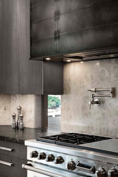 A Black Metal Range Hood Is Flanked By Dark Gray Modern Cabinets