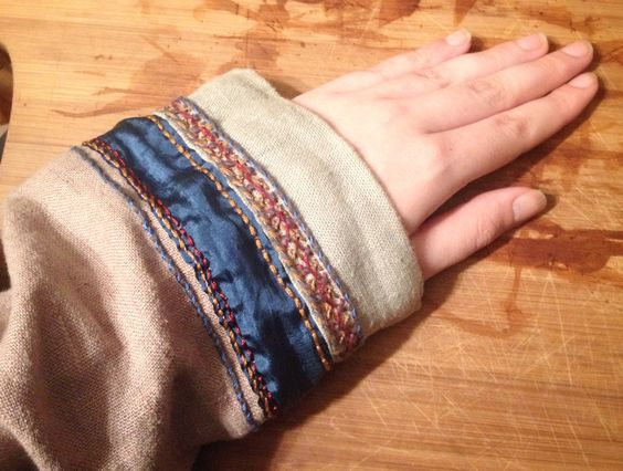 Viking dress cuff with blue silk, embroidered using stitches from the mammen find, including a double herringbone stitch.