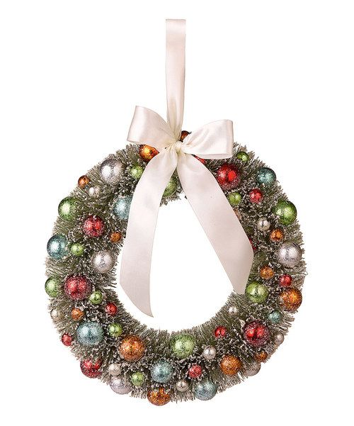 Designed with shiny ball ornaments, frosty dusting and a bright bow tie, this wreath fills a home with good tidings and cheer. 12'' diameterNatural fibers / PVCImported