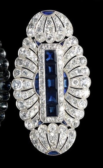 A sapphire and diamond plaque brooch, circa 1915. The scalloped, rounded lozenge, composed of pierced palmette motifs, millegrain-set with old brilliant and single-cut diamonds, with a central row of square-cut sapphires and calibré-cut sapphire accents, mounted in platinum, diamonds approximately 6.60 carats total, diameter 6.2cm.