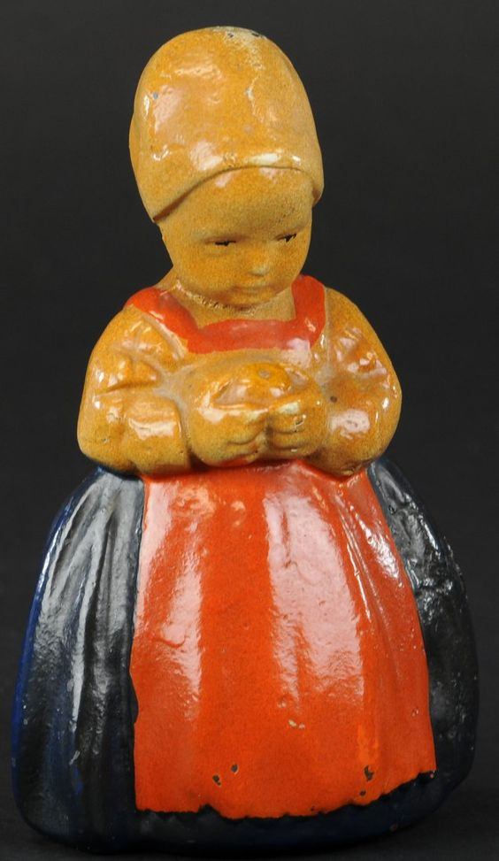 DUTCH GIRL DOORSTOP                        Young girl in dress & bonnet, holding flowers with bow in hair. 6 1/2 h.