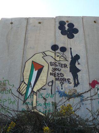 Grafite de Banksy no muro israelense na Cisjordânia mostra garota voando para o outro lado do muro por meio de balões