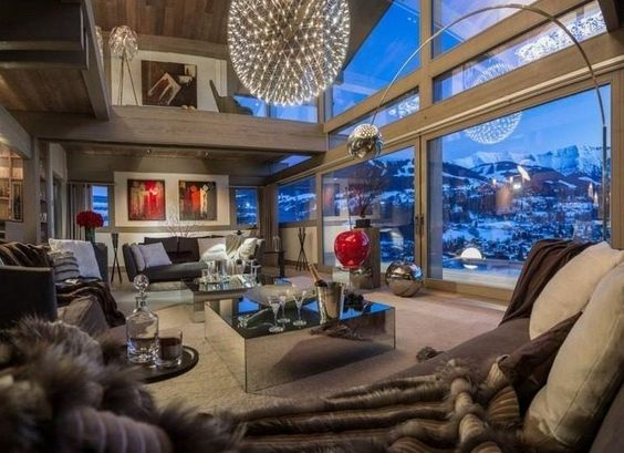 This ski chalet in the Rhone-Alpes, France has double heigh ceilings, a hanging globe light, glass railings, colorful artwork, a mirrored coffee table and a wall of glass overlooking the mountains.