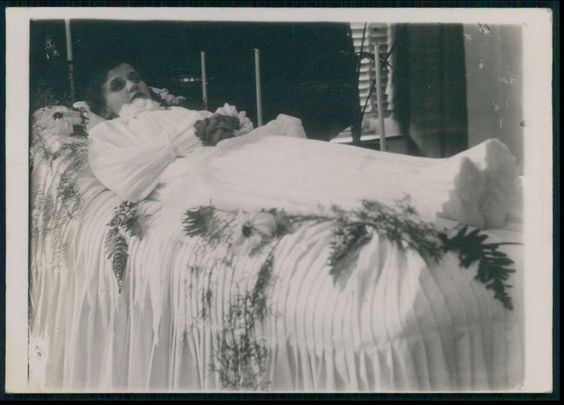 1917, Young woman laid out in ruffled dress