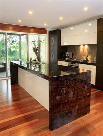 The waterfall look to the granite in this island is not just unique, but also adds something of a hard and polished look to this modern kitchen. White and black combined with sharp angles definitely create a unique impression.