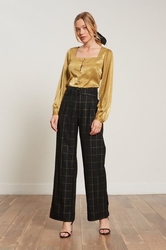 FINAL SALE Black with gold plaid print belted trouser. Features Polyester blend Zip up Wide Leg Belted at waist Model is wearing size x-small This style has an impeccable fit! Fabric Garment Care Each item we make is produced and handled with care. We encourage you to consider the environment when cleaning our items. We recommend you hand wash this product and hang to dry.