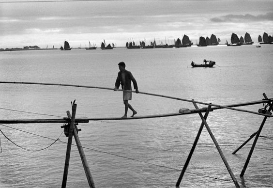 Werner Bischof. HONG-KONG. 1952. Man balancing above the water like a tight rope walker.
