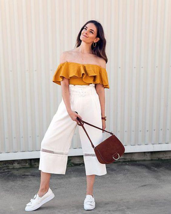Como usar amarelo em diversos looks: guia completo. Blusa com decote ombro a ombro, ciganinha, calça pantacourt branca, tênis branco