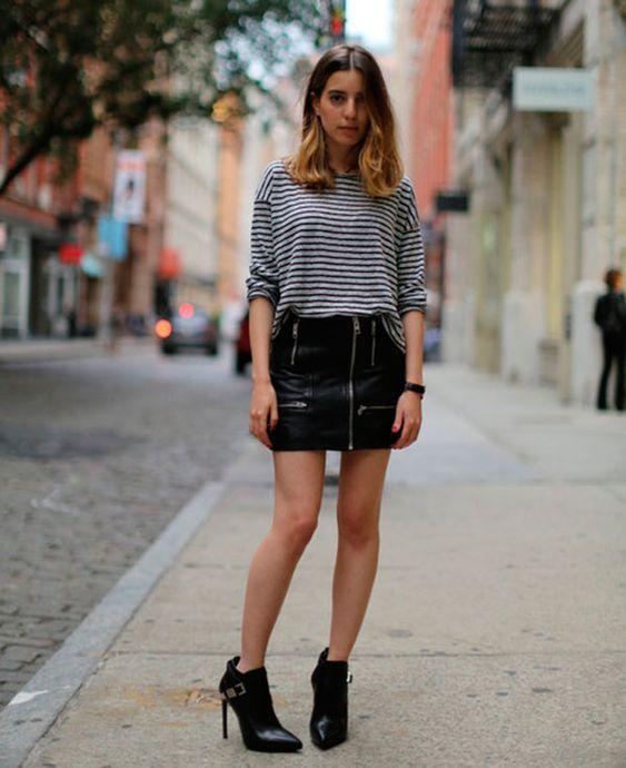 Sarah Nait parada na rua veste saia de couro com ziper, blusa de listras e botas pretas