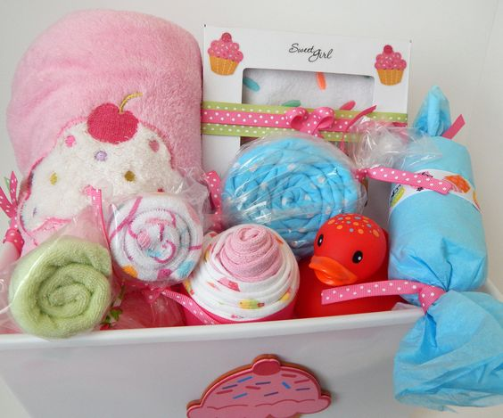 lovely baby items folded as candies inside this cupcake baby gift basket