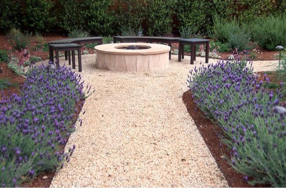 This warm and perfectly neat 'Salmon Bay' gravel path, beautifully framed by 'Otto Quast' Spanish lavender and other Mediterranean plantings, creates a rustic outdoor room for the fire pit area.