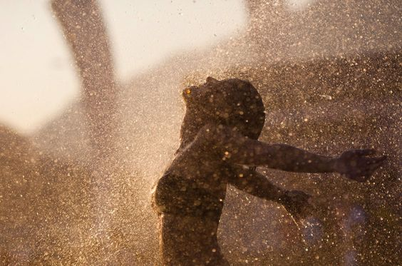 A woman walks into a spray of water to get relief from the heat during the Rock in Rio music festival in Rio de Janeiro, Brazil, on October 1, 2011. (AP Photo/Felipe Dana)