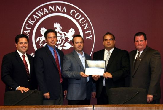 Jeffrey Mando, inside right, Lackawanna County's Director of Information Technology, accepts the County's national Digital Government Award in recognition of the major technology upgrades, wireless advances, and overall innovations achieved through computer communications. This is the second year in a row that the County's department finished in the top five in the 150,000 – 249,999 population category.