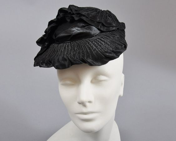 Flat hat toque or topper from the 1940's (front view)   Label: Muhlfelder   Nicely detailed with crimped black satin, ribbons, and an overall complex draping design on a black hat felt base   Sometimes called an Eleanor Roosevelt hat as she wore this style quite a lot
