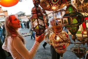 A woman browsing for Moroccan lanterns in a market stall in the souk.