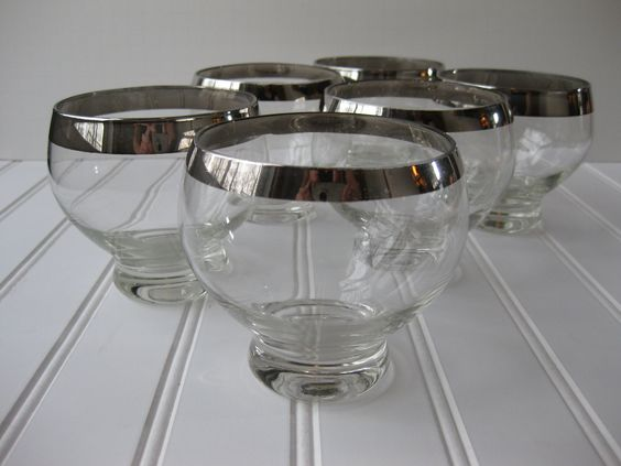 Hey Joy, Saw these and they are kinda similar to what you were looking for.  Vintage Silver Trimmed Bar Glasses Set of Six. $47.50, via Etsy.