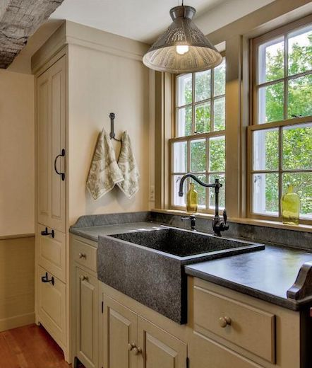 Slate countertops and apron sink in farmhouse kitchen.