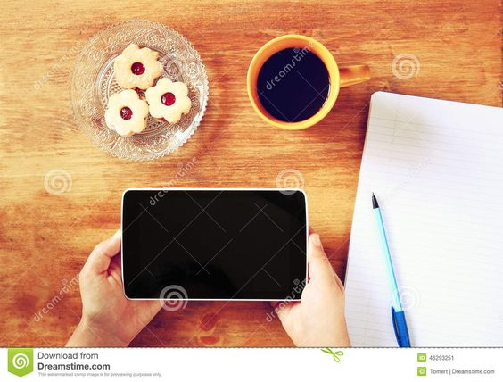 top view - hands holding tablet - notebook - pen - coffee - pastry