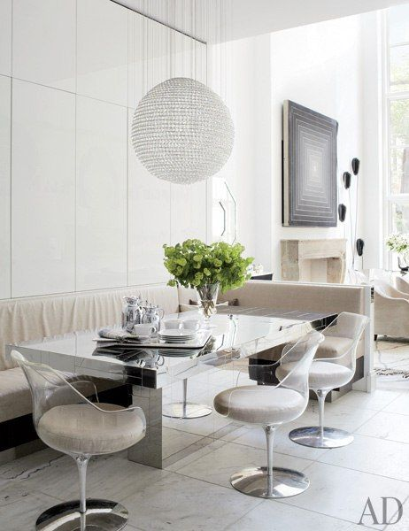 Delphine Krakoff renovates a Manhattan residence.Table by Paul Evans, banquette in Holly Hunt fabric, Erwine and Estelle Laverne chairs; pendant light by Tom Dixon for Swarovski, marble tiles.