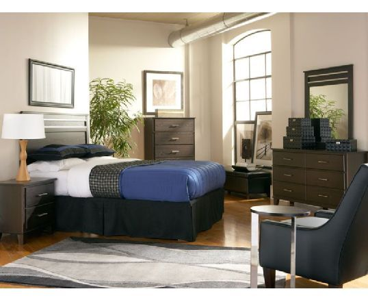 Look to the Dakota Skyline Queen bedroom for a smart design that always looks put together. The contemporary style headboard has a distinctive horizontal slat detailing at the top. With 6 deep drawers, the wide profile dresser offers ample clothing storage. <br><br>For balanced design, the portrait style mirror replicates the elegant slat top detailing. Bedside, the matching brown nightstand has 2 convenient storage drawers with sleek silver bar pulls. A stylish table lamp selected by…