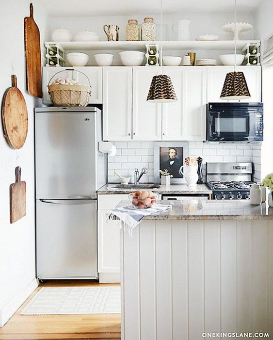 Kitschy country accessories give this compact kitchen an eclectic pastoral vibe, but the foundations of it—subway tile, granite counters, and white beadboard. #smallkitchens