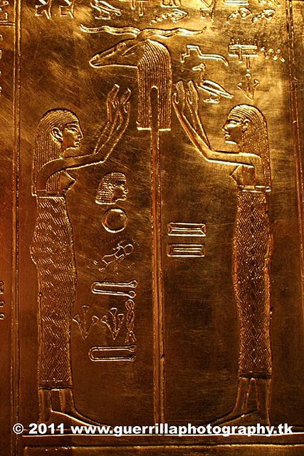 2 female deities of the Amentet, hands raised towards the Ram head on the standard of Khnoum the fashioner of forms in the womb, in hope that the king would rise once more from the waters of non-existence. Form Tutankhamun's gold shrine.